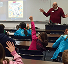 Photo showing an LES presenter engaging students with a game of Energy-efficiency Jeopardy